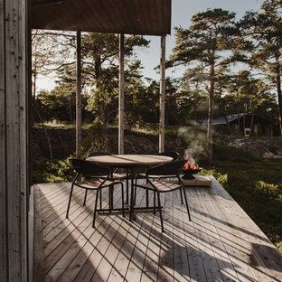 Deck - large scandinavian side yard deck idea in Stockholm with a roof extension