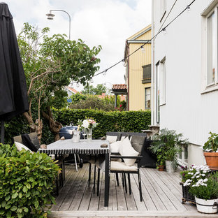 Example of a mid-sized danish deck design in Gothenburg with no cover