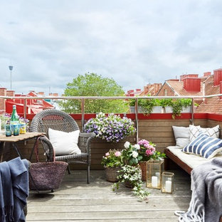Example of a mid-sized danish deck container garden design in Gothenburg with no cover