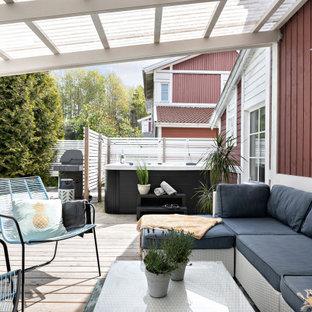 Minimalistisk inredning av en stor terrass på baksidan av huset, med en pergola