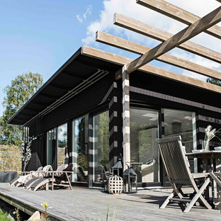 This is an example of a medium sized scandinavian back terrace and balcony in Stockholm with a pergola.