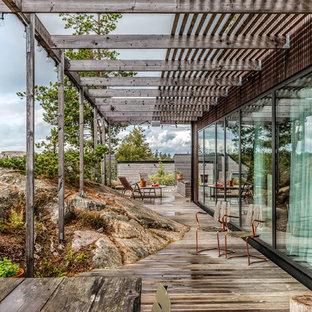 Inspiration för en mellanstor minimalistisk terrass på baksidan av huset, med en pergola