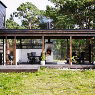 Example of a mid-sized danish rooftop deck design in Stockholm with a fire pit and no cover