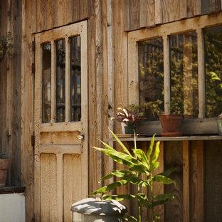 Foto di un grande patio o portico stile shabby con un giardino in vaso e una pergola