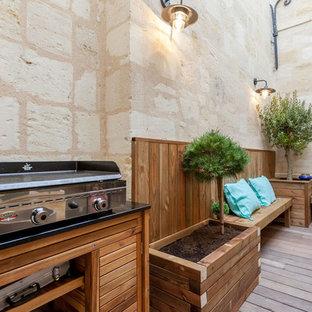 Cette photo montre une terrasse avec une cuisine extérieure arrière tendance de taille moyenne avec aucune couverture.