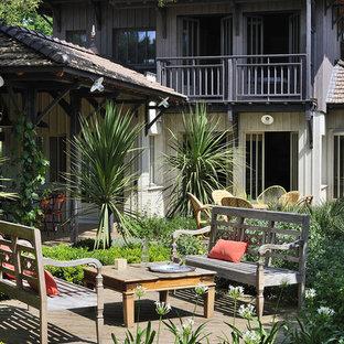 Exemple d'une terrasse arrière chic de taille moyenne avec une terrasse en bois et une extension de toiture.