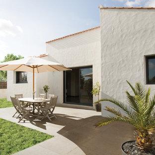 Inspiration pour une terrasse avec des plantes en pots arrière méditerranéenne de taille moyenne avec du carrelage et aucune couverture.