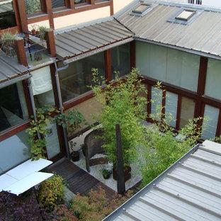 Esempio di un grande patio o portico etnico in cortile con ghiaia, un giardino in vaso e un tetto a sbalzo