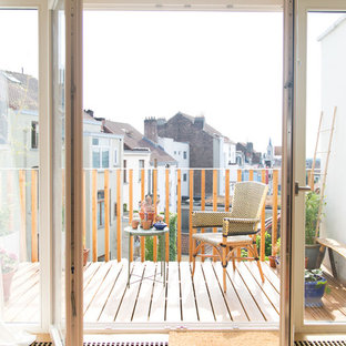 Mid-sized danish backyard deck container garden photo in Brussels with an awning