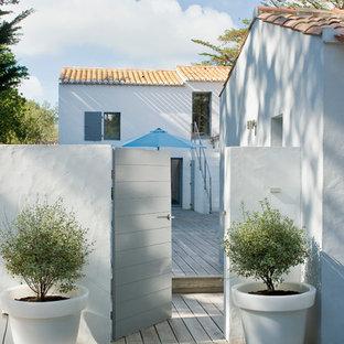 Cette image montre une terrasse avec des plantes en pots arrière marine de taille moyenne.