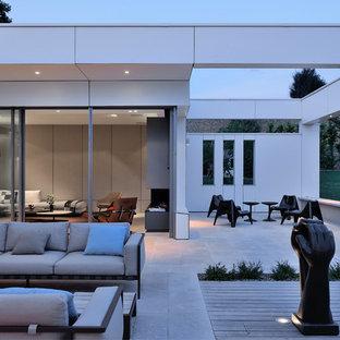 Réalisation d'une grande terrasse arrière design avec des pavés en pierre naturelle et aucune couverture.