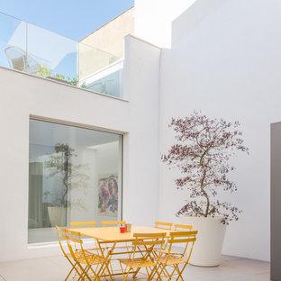 Inspiration pour une terrasse minimaliste de taille moyenne avec une cour, du carrelage et aucune couverture.