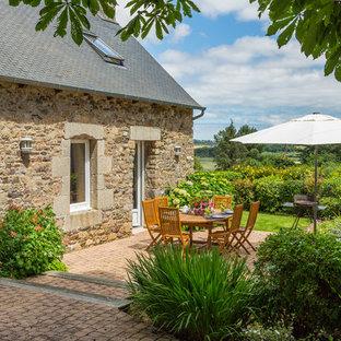 Exemple d'une terrasse arrière nature avec des pavés en brique et aucune couverture.