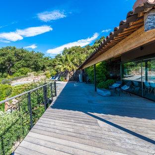 Exemple d'une très grande terrasse et balcon tendance avec une extension de toiture.