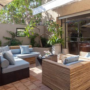 Idée de décoration pour une terrasse avec des plantes en pots design de taille moyenne avec des pavés en pierre naturelle et un auvent.