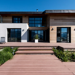 Cette image montre une grande terrasse avec des plantes en pots arrière design avec une extension de toiture.