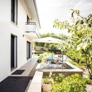 Cette image montre une terrasse latérale design de taille moyenne avec une terrasse en bois.