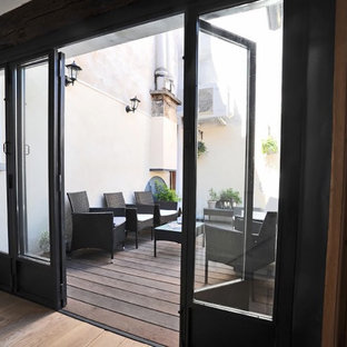 Mid-sized farmhouse courtyard deck container garden photo in Paris with no cover