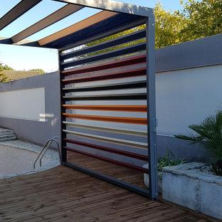 Ispirazione per una terrazza industriale di medie dimensioni e dietro casa con una pergola
