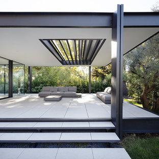 Idées déco pour une terrasse avant moderne de taille moyenne avec du carrelage et une extension de toiture.