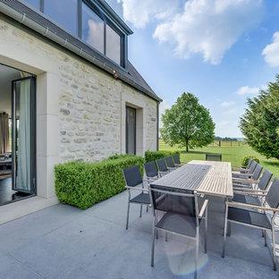 Idées déco pour une grande terrasse et balcon arrière contemporaine avec aucune couverture et des pavés en pierre naturelle.