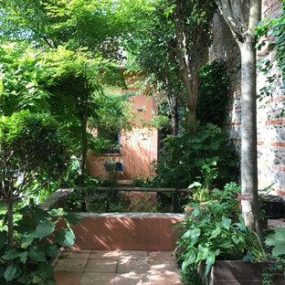 Cette photo montre une petite terrasse romantique avec un foyer extérieur.
