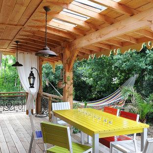 Inspiration pour une grande terrasse arrière bohème avec une extension de toiture.