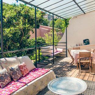 Aménagement d'une terrasse arrière contemporaine de taille moyenne avec un auvent et un foyer extérieur.