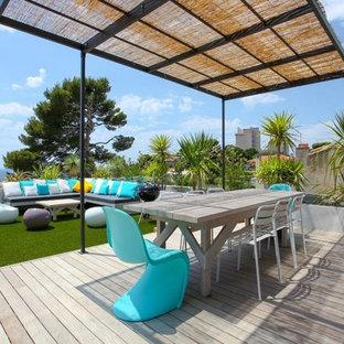 Exemple d'un grand toit terrasse bord de mer avec une pergola.