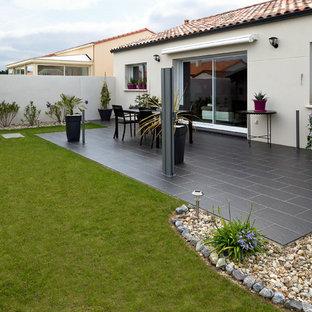 Imagen de patio minimalista, de tamaño medio, en patio trasero y anexo de casas, con jardín de macetas y losas de hormigón