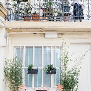 Ispirazione per un piccolo patio o portico industriale davanti casa con un giardino in vaso e piastrelle