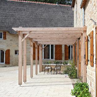 Exemple d'une terrasse nature avec une pergola.