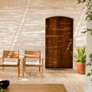 Idée de décoration pour une terrasse avec des plantes en pots méditerranéenne de taille moyenne avec des pavés en pierre naturelle, un auvent et une cour.