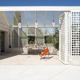 Cette image montre une terrasse latérale design de taille moyenne avec une dalle de béton et une pergola.
