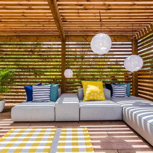 Idée de décoration pour une terrasse design avec une terrasse en bois et un gazebo ou pavillon.