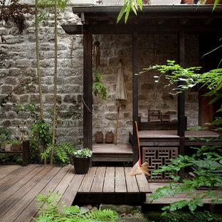 Aménagement d'une grande terrasse avec des plantes en pots latérale asiatique avec un auvent.