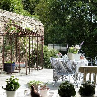 Réalisation d'une terrasse avec des plantes en pots champêtre de taille moyenne avec aucune couverture.