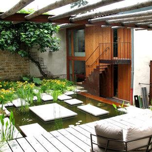 Idées déco pour une terrasse arrière éclectique de taille moyenne avec un point d'eau, une terrasse en bois et une pergola.