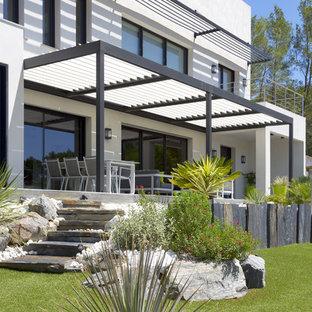 Cette photo montre une terrasse avant tendance avec une pergola.