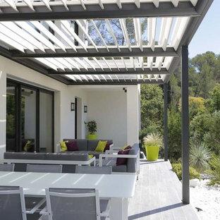 Immagine di un patio o portico design davanti casa con un giardino in vaso, graniglia di granito e una pergola