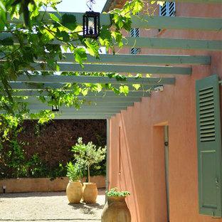Réalisation d'une terrasse avec des plantes en pots avant méditerranéenne de taille moyenne avec du gravier et une pergola.