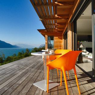 Cette photo montre une terrasse arrière tendance de taille moyenne avec une extension de toiture.