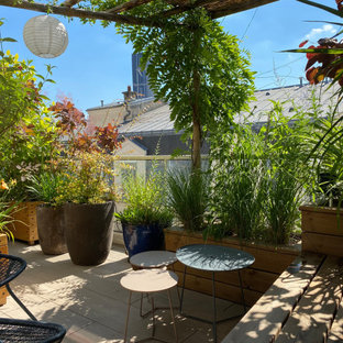 Deck container garden - mid-sized shabby-chic style side yard deck container garden idea in Paris with a pergola