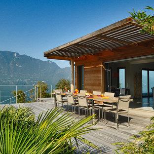 Cette photo montre une grande terrasse et balcon latérale tendance avec une pergola.
