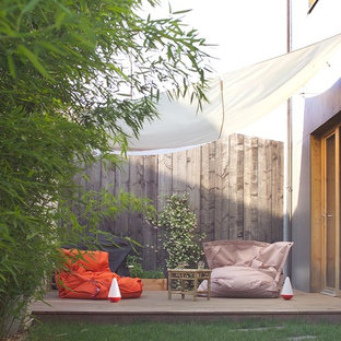 Exemple d'une terrasse latérale tendance de taille moyenne avec une terrasse en bois et un auvent.