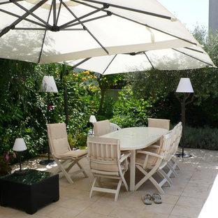 Esempio di un grande patio o portico minimal dietro casa con piastrelle e un parasole