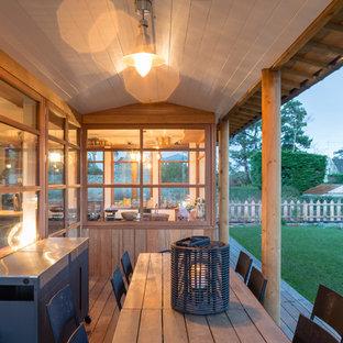 Inspiration pour une terrasse avec une cuisine extérieure arrière rustique de taille moyenne avec une extension de toiture.
