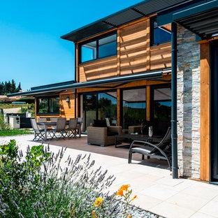 Idées déco pour une terrasse arrière contemporaine de taille moyenne avec un auvent.