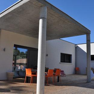 Inspiration pour une terrasse arrière design de taille moyenne avec une extension de toiture.