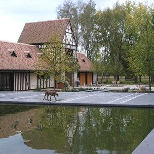 Réalisation d'une grande terrasse tradition avec un point d'eau, du carrelage et aucune couverture.